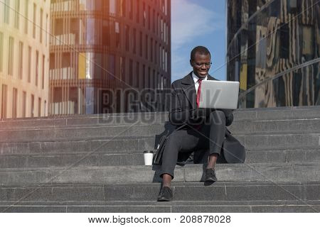 Horizontal Closeup Of Young African American Businessman Sitting Outdoors On Stairs With Laptop Open