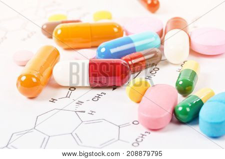 Heap of color pills and tablets on chemical formulas background