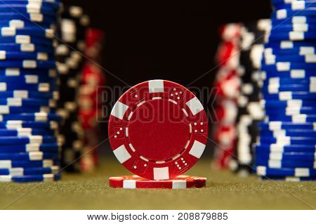 Closeup of poker chips on green felt card table surface