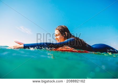 Surf girl is smiling and rowing on the surfboard. Woman with surfboard in ocean during surfing. Surfer and ocean