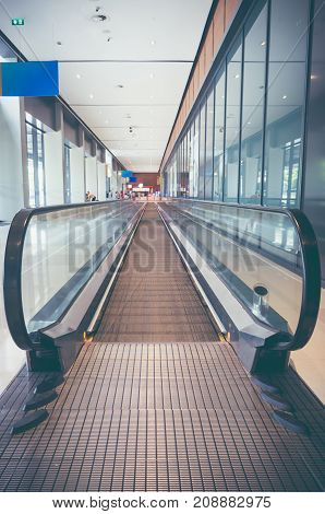 Modern long walkway of escalator moving forward at international airport terminal. Vintage film filter effect.