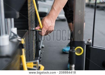 Young Man Execute Exercise With Pull Down Machine In Fitness Center. Male Athlete Select Weight For