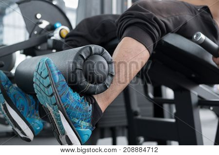Young Man Execute Exercise With Weightlifting Machine In Fitness Center. Male Athlete Pump Up Leg Mu