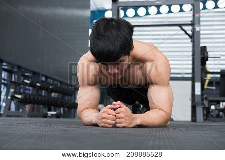 Muscle Man Doing Plank Position In Gym. Bodybuilder Male Working Out In Fitness Center. Athlete Doin