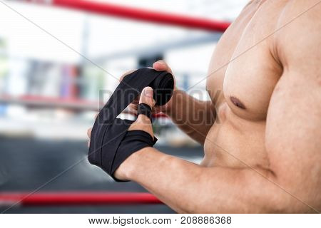 Male Fighter Wear Bandages On Fist. Muscular Man Bind Bandage On Hand Before Training. Sportsman Pre