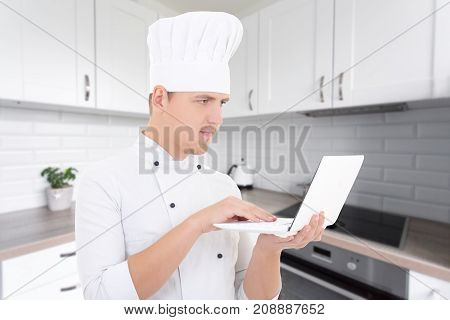 Blogger Concept - Young Man Chef In Uniform With Laptop In Modern Kitchen