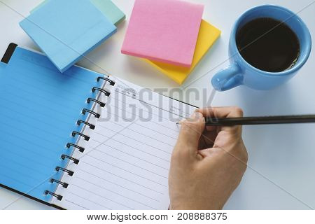Hand holding pencil and writing in a diary notebook on the white desk with coffee and colorful of note pad