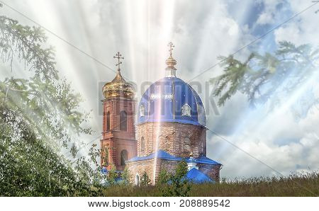 the old Church of red brick with blue and gold domes and crosses on the domes on the background sky with clouds in the rays of the sun