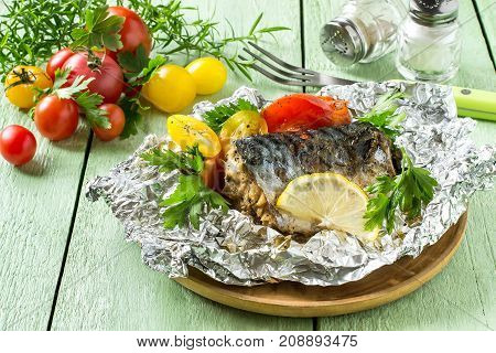 Mackerel baked with tomatoes in foil. Mackerel in foil lies on wooden plate on green wooden table. Also lie fresh tomatoes herbs fork containers for salt and pepper. Healthy and dietary food