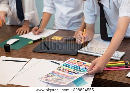 Graphic Or Interior Designer Choosing A Colour From Color Swatch Sampler Or Catalogue Palette Guide.