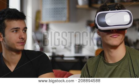 Two young men posing on sofa and experimenting VR glasses while spending time together.