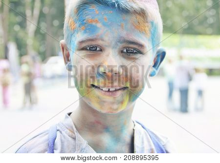 Portrait of a smiling teenage boy with multi-colored face at the festival in the park.Toning