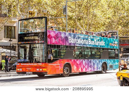 BARCELONA, SPAIN - August 16, 2017: Barcelona city tour bus with people on the street in Barcelona city