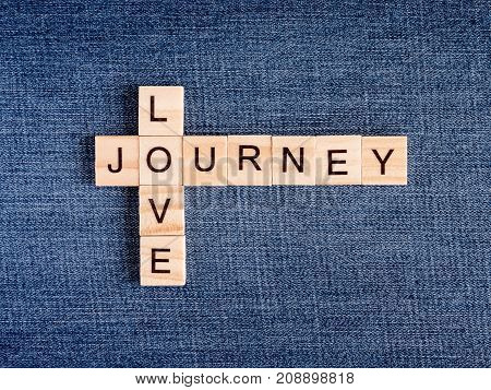 Wooden cubes crossword of Love Journey on Jean fabric background