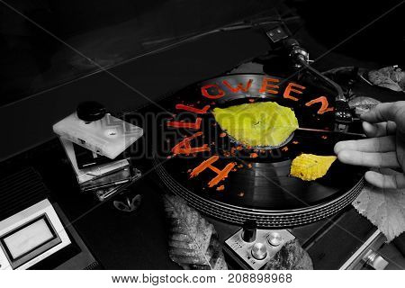 DJ hand playing vinyl with Halloween writing on it selective color closeup