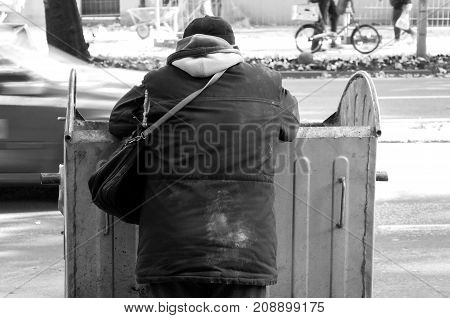 Homelessness. Poor and hungry homeless man in dirty clothes looking for food in the dumpster on the urban street in the city black and white