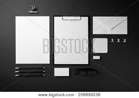 Branding stationery mockup on black paper background. Blank objects for placing your design. Top view.