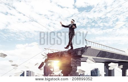 Businessman walking blindfolded among flying paper planes on concrete bridge with huge gap as symbol of hidden threats and risks. Cityscape and sunlight on background. 3D rendering.