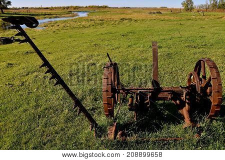 Remains of an old rusty horse drawn hay mower missing some parts is left in the pasture