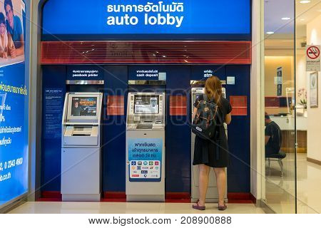 Mega Bangna Shopping Center Bangkok Thailand - October 7 2017: Woman standing cash at bank automatic teller machines. Automatic cash machines or ATMs are very popular nowadays. It is easy to use and comfortable to lifestyle.