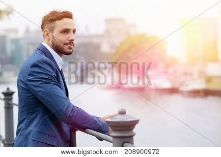 handsome dark-haired businessman standing by the river