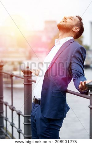 handsome dark-haired businessman standing by the river and enjoying the sun