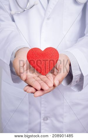 Young Asian doctor stand holding a red heart with two hands. Dress up with doctor gown uniform with stethoscope in a hospital. Beautiful Asia female model in her 20s anonymous face