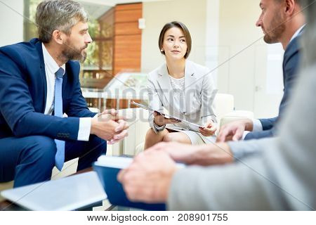 Attractive mixed race woman in formalwear presenting her point of view concerning start-up project while gathered together with male colleagues at spacious meeting room