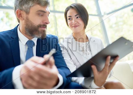 Pretty young manager and her middle-aged bearded colleague analyzing results of accomplished work while having working meeting at boardroom, she looking at him with charming smile