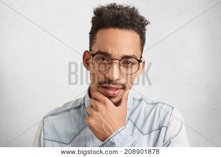 Indoor Portrait Of Confident Thoughtful Male Freelancer Keeps Hand On Chin, Tries To Decide What Do