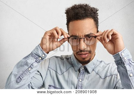 Confident Mixed Race Male Enterpreneur Keeps Hands On Frames Of Glasses, Looks Attentively At You, A