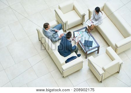 Directly above view of hard-working business people discussing joint project while having informal meeting at spacious office lobby