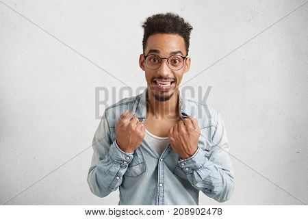 Image Of Cheerful Male With Oval Face, Wears Round Spectacles, Tears Off Shirt, Being Hot After Runn