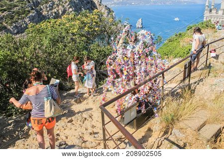 Yalta, Crimea - 11 July, People at the tree of desires, 11 July, 2017. Small Castle Lastochkino Nest and its surroundings.