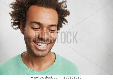 Headshot Of Shy Dark Skinned Male With Crisp Hair, Smiles Broadly, Shows White Even Teeth, Looks Dow