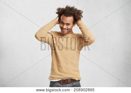 Glad Shy Male With Trendy Hairdo Wears Sweater And Jeans Feels Awkward As Has First Date With Girlfr
