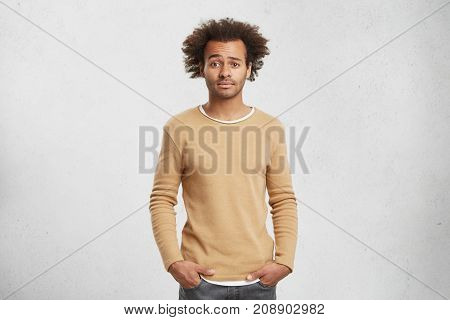 Portrait Of Puzzled Young Dark Skined Afro American Male Wears Fashionable Clothes, Keeps Hands In P