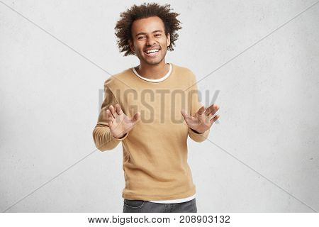 Cheerful Handsome African American Male Has Crisp Hair, Dressed Casually, Smiles Happily As Sees Com