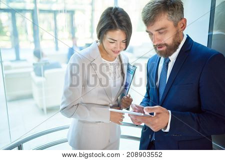 Pretty mixed race woman and her bearded colleague using digital tablet in order to discuss joint project while going up in glass elevator