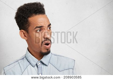 Young Handsome Man With Oval Long Face, Beard And Mustache, Looks Indignant And In Disgusted Express