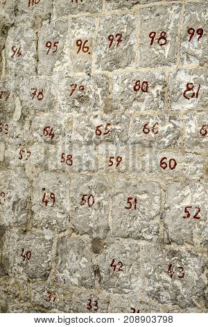 Stone wall with numbered stones. Two-digit red numbers on the stones. Restoration of the wall.