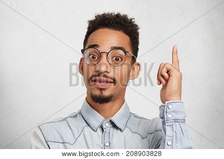 Young Male Clever Student Wears Glasses And Denim Shirt, Raises Index Finger As Gets Idea How To Mak