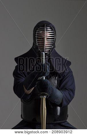 Portrait of man kendo fighter with bamboo sword in traditional uniform. Shot in studio.