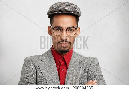 Close Up Portrait Of Confident Serious Man Has Dark Beard And Mustache, Wears Trendy Spectacles, Red