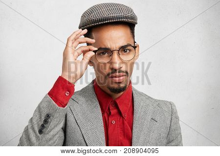Convinced Self Assured Black Macho Man Wears Trendy Glasses, Cap And Jacket, Comes On Meeting With B