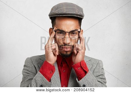 Horizontal Shot Of Pensive Mixed Race Man Dressed Formally, Keeps Fingers On Temples, Looks Seriousl