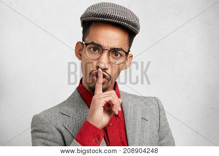 Funny Male With Dark Healthy Skin Wears Round Spectacles, Keeps Finger On Lips, Makes Silence Sign,