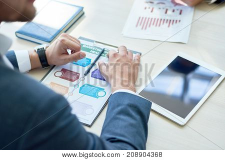 Over shoulder view of unrecognizable businessman sitting at boardroom table while having working meeting with colleagues, close-up shot
