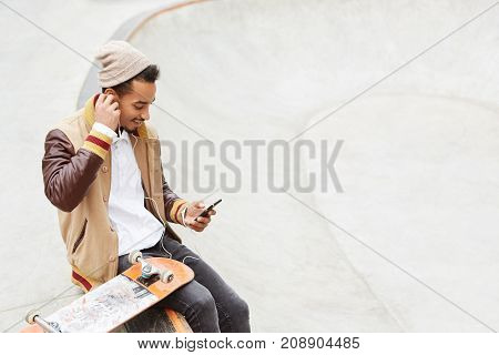 Urban Stylish Hipster Guy Sits Near His Skateboard, Wears Trendy Clothes, Makes Video Call On Mobile
