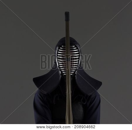 male in tradition kendo armor with bamboo sword . shot in studio on grey background